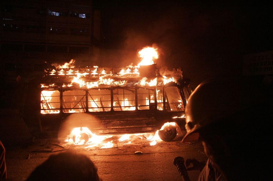A vehicle burns after being set on fire by protesters following the killing of a local leader of the Muttahida Quami Movement, in Karachi, Pakistan, on Monday, Aug. 2, 2010. More than 40 people were killed in revenge attacks. (AP Photo/Shakil Adil)