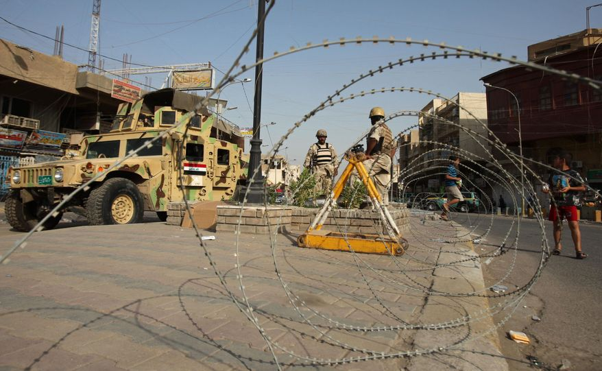 Iraqi army soldiers secure a street in the Azamiyah neighborhood in Baghdad on Saturday. Authorities announced a partial lifting of a curfew imposed on the Sunni neighborhood. (Associated Press)