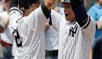 New York Yankees' Alex Rodriguez looks on as fans cheer in the background after hitting his 600th career home run during the first inning of a baseball game against the Toronto Blue Jays at Yankee Stadium on Wednesday, Aug. 4, 2010 in New York.  (AP Photo/Kathy Willens)