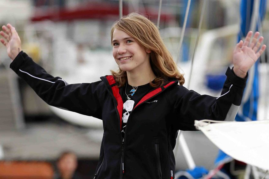 Laura Dekker waves to the media as she stands on her boat in Den Osse, southwest Netherlands, Wednesday, Aug. 4, 2010. Fourteen year-old Laura Dekker, who hopes to become the youngest person to sail around the world by herself, and her father Dick Dekker, have departed the harbor of Den Osse in her 38-foot (11.5-meter) yacht Guppy, bound for Portugal where she hopes to begin her solo attempt later this year. (AP Photo/Bas Czerwinski)