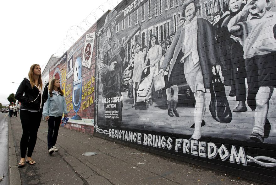 In this photo taken Tuesday, Aug. 3, 2010, Mary Seaman, left, from New York and Kristen Roche from Connecticut visit murals on the Falls Road in West Belfast, Northern Ireland. Teenagers who lost loved ones in acts of terror worldwide are camping together this week in Northern Ireland as they learn to move beyond their grief and become peacemakers themselves. (AP Photo/Peter Morrison)
