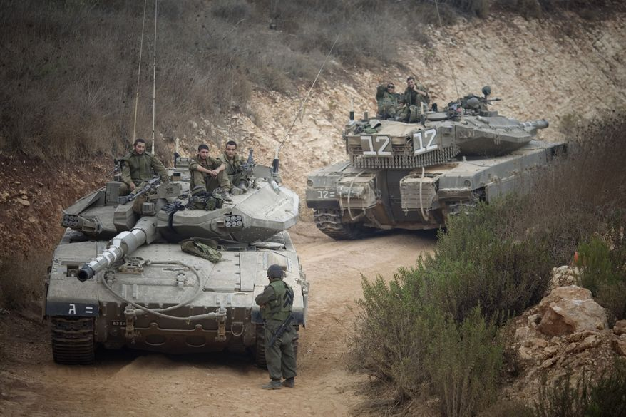 Israeli soldiers sit on top of their tank near the site of an exchange of fire between Israeli and Lebanese troops along the border between Israel and Lebanon, Wednesday, Aug. 4, 2010. Lebanese and Israeli troops exchanged fire Tuesday in a fierce border battle that killed a senior Israeli officer, two Lebanese soldiers and a journalist underlining how easily tensions can re-ignite along the frontier where Israel and Hezbollah fought a war four years ago. (AP Photo/Ariel Schalit)