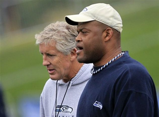 In this photo taken Monday, Aug. 2, 2010, Seattle Seahawks linebackers coach Ken Norton Jr. yells during an NFL football training camp in Renton, Wash. The fiery former Cowboys champion and 49ers Pro Bowl hitter is back in the NFL, following Pete Carroll from USC to Seattle. His barks at his defenders and taunts at the offense is louder and more constant than the music Carroll is thumping throughout training camp. (AP Photo/Elaine Thompson)