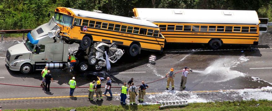 Associated Press Emergency workers respond to an accident involving two school buses, a tractor trailer and a pickup truck Thursday on I-44 near Gray Summit, Mo. The school buses, carrying high school students, couldn't avoid a wreck of the trucks that had occurred in front of them.