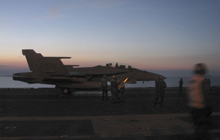 A flight deck crew aboard the USS George Washington work on an F/A-18 during joint maneuvers with South Korea off the peninsula's east coast on July 25, 2010. (AP Photo/Eric Talmadge)