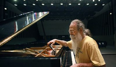 In this July 26, 2010 photo, piano tuner Bill Calhoun, who is marking his 25th anniversary this year as the piano tuner for the Newport Jazz Festival, poses for a portrait at a piano in an empty concert hall on the campus of the University of Rhode Island, in South Kingston, R.I. (AP Photo/Steven Senne)