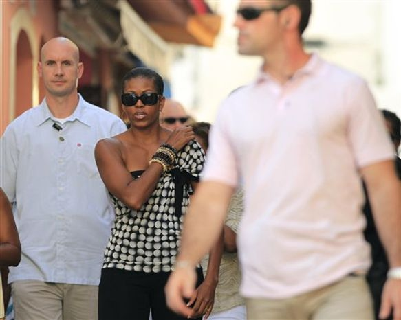 US first lady Michelle Obama, center, walks down a street as she visits Marbella, in southern Spain. Wednesday, Aug. 4, 2010. The White House says first lady Michelle Obama is in Spain for a private trip with longtime family friends. (AP Photo/Sergio Torres)