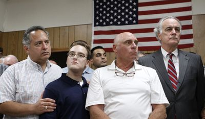 Hartford Distributors operations executive Steve Hollander, left, puts a hand on his son Brett's shoulder, as the company's co-owner Jim Stack, second from right, and attorney Bud O'donnell, right, listen during a press conference at a union hall, in South Windsor, Thursday, Aug. 5, 2010. (AP Photo/Steven Senne)