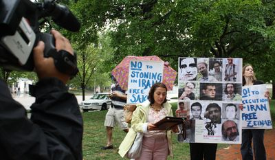 Shirin Nariman, a former Iranian political prisoner, speaks out on Thursday, August 5, 2010, against the Iranian regime's executions and methods of torture to a group of about 15 Iranian activists while some stand behind her, holding posters of political prisoners sentenced to death.
