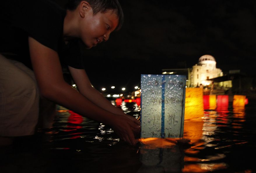 With the gutted Atomic Bomb Dome in the background, a boy releases a paper lantern on the Motoyasu River for a memorial service of the atomic bomb victims in Hiroshima, western Japan, Friday, Aug. 6, 2010. Hiroshima marks the 65th anniversary of the the world's first atomic bomb attack that devastated the western Japanese city at the closing days of World War II. (AP Photo/Shuji Kajiyama)
