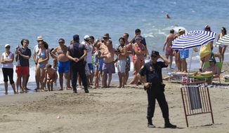 Police officers keep onlookers away from the site where U.S. First Lady Michelle Obama and daughter Sasha stay at the Beach Club of Villa Padierna Hotel in Marbella, southern Spain, on Friday, Aug. 6, 2010. (AP Photo/Sergio Torres)