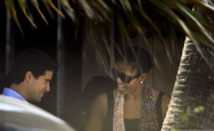 First lady Michelle Obama, right, speaks with an unidentified person at the Beach Club of Villa Padierna Hotel in Marbella, southern Spain, on Friday, Aug. 6, 2010. (AP Photo/Sergio Torres)