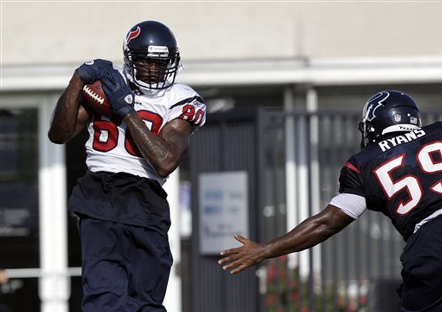 Houston Texans wide receiver Andre Johnson (80) catches a pass as linebacker DeMeco Ryans (59) defends during a NFL football training camp practice Thursday, Aug. 5, 2010,  in Houston. (AP Photo/David J. Phillip)