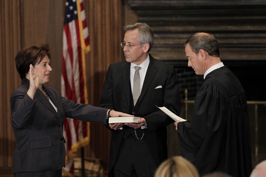 Elena Kagan is sworn in as the Supreme Court's newest member as Chief Justice John Roberts, right, administers the judicial oath, at the Supreme Court Building in Washington, Saturday, Aug. 7, 2010. The Bible is held by Jeffrey Minear, center, counselor to the chief justice. Kagan, 50, who replaces retired Justice John Paul Stevens, becomes the fourth woman to sit on the high court, and is the first Supreme Court justice in nearly four decades with no previous experience as a judge. (AP Photo/J. Scott Applewhite)