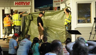 The sauna and the final two competitors, Finland's Timo Kaukonen and Russia's Vladimir Ladyzhenskiy, are shielded by a tarpaulin at the finals of the World Sauna Championships in Heinola, Finland, on Saturday, Aug. 7, 2010. Organizers said Mr. Ladyzhenskiy collapsed and died, while his Finnish rival was rushed to a hospital. (AP Photo/LEHTIKUVA/Sari Gustafsson)