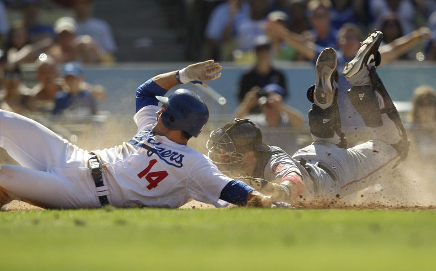 ASSOCIATED PRESS Los Angeles Dodgers' Jamey Carroll, left, scores on teammate Reed Johnson's single as Washington Nationals catcher Wil Nieves, right, applies a late tag during the eighth inning of a baseball game in Los Angeles, Sunday, Aug. 8, 2010.