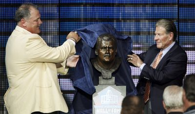 Former Washington Redskins player Russ Grimm (left) unveils a bust of himself with help from former Redskins coach Joe Bugel during Grimm's enshrinement in the Pro Football Hall of Fame in Canton, Ohio, on Saturday, Aug. 7, 2010. (AP Photo/Ron Schwane)