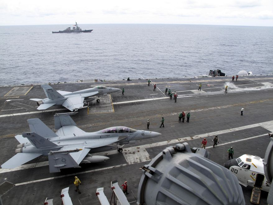 American fighter jets prepare to take off from the USS George Washington, cruising in the South China Sea about 200 miles off Vietnam's central coast on Sunday, Aug. 8, 2010. (AP Photo/Margie Mason)