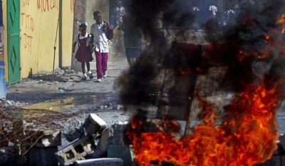 Students walk by burning debris set afire in protest of the Haitian government's lack of help to rebuild the area after the earthquake in Port-au-Prince. Education is one of the areas Haitian candidate for president Wyclef Jean hopes to improve. (Associated Press)