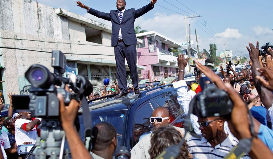 ** FILE ** Haitian-born singer Wyclef Jean greets supporters after he submitted paperwork to run for president of Haiti in early August. Mr. Jean, who left Haiti as a child, said he would like to focus on Haiti's economy, which would include creating jobs in the garment-export industry. (AP Photo)
