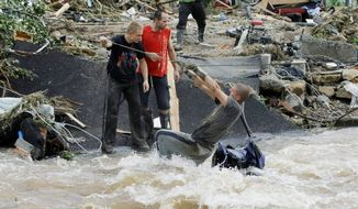 A resident of Bogatynia, Poland, uses a rope to get across a fast-flowing but receding river Monday after a bridge collapsed in flash floods that killed at least 11 people and left towns in Poland, the Czech Republic and Germany strewn with rubble and coping with badly damaged homes and roads. (Associated Press)