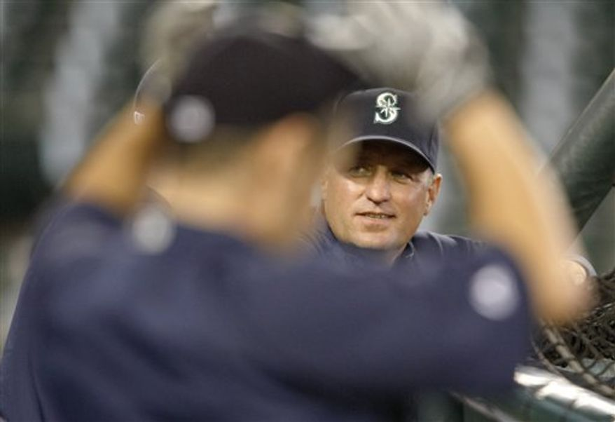 Seattle Mariners interim manager Daren Brown, back, is framed by Ichiro Suzuki in the foreground during batting practice before a baseball game against the Oakland Athletics  in Seattle Monday, Aug. 9, 2010. Brown replaces Don Wakamatsu who was fired today. (AP Photo/John Froschauer)