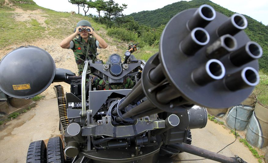 A South Korean marine surveys the situation behind a vulcan automatic cannon during an exercise on Baengnyeong Island, northwest of Seoul near the border with North Korea, on Sunday, Aug. 8, 2010. South Korean troops fired artillery and dropped sonar buoys into the Yellow Sea as naval drills kicked off near the spot where a warship sank four months ago. (AP Photo/Yonhap, Seo Myung-gon)