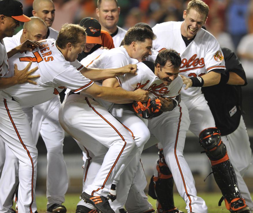 ASSOCIATED PRESS Baltimore Orioles Brian Roberts, center, is mobbed by team mates including Matt Albers, left, and Luke Scott, left center, after hitting a game winning solo home run against the Chicago White Sox in the 10th inning of a baseball game Monday, Aug. 9, 2010 in Baltimore. Orioles won 3-2.