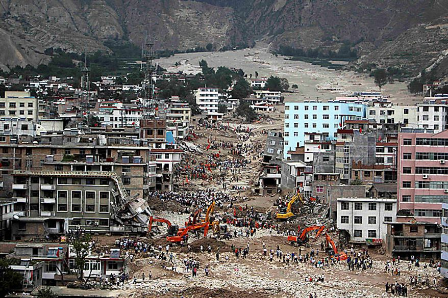 Rescue workers search among the debris after a mudslide swept away a large part of the town of Zhouqu, Gannan prefecture, in northwestern China's Gansu province, on Monday, Aug. 9, 2010. Rescuers dug through mud and wreckage Monday searching for hundreds of people missing after flash floods and landslides struck northwestern China. (AP Photo)