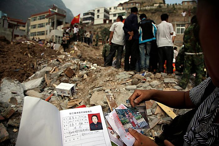 Residents examine personal belongings recovered from houses destroyed after a mudslide that swept through the town of Zhouqu in Gannan prefecture of northwestern China's Gansu province on Monday, Aug. 9, 2010. Rescuers dug through mud and wreckage Monday searching for 1,300 people missing after flash floods and landslides struck northwestern China. (AP Photo/Ng Han Guan)