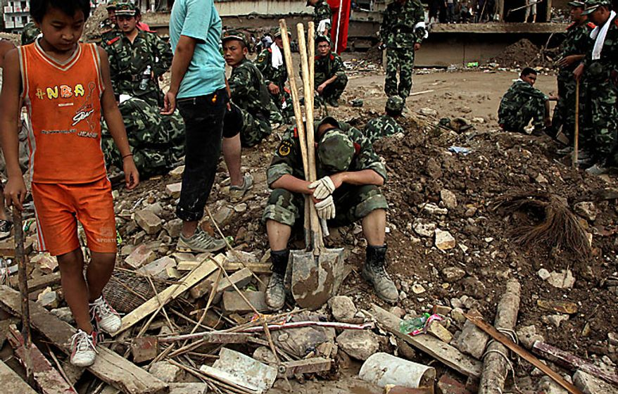 A paramilitary policeman rests among the debris of buildings destroyed by a mudslide that swept through the town of Zhouqu in Gannan prefecture of northwestern China's Gansu province on Monday, Aug. 9, 2010. Rescuers dug through mud and wreckage Monday searching for 1,300 people missing after flash floods and landslides struck northwestern China. (AP Photo/Ng Han Guan)