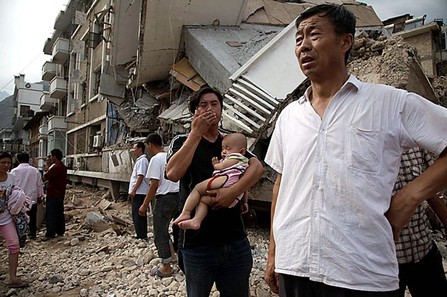 A Chinese man reacts as he carries a child near a building destroyed by a mudslide that swept through the town of Zhouqu in Gannan prefecture of northwestern China's Gansu province on Monday, Aug. 9, 2010. Rescuers dug through mud and wreckage Monday searching for 1,300 people missing after flash floods and landslides struck northwestern China. (AP Photo/Ng Han Guan)