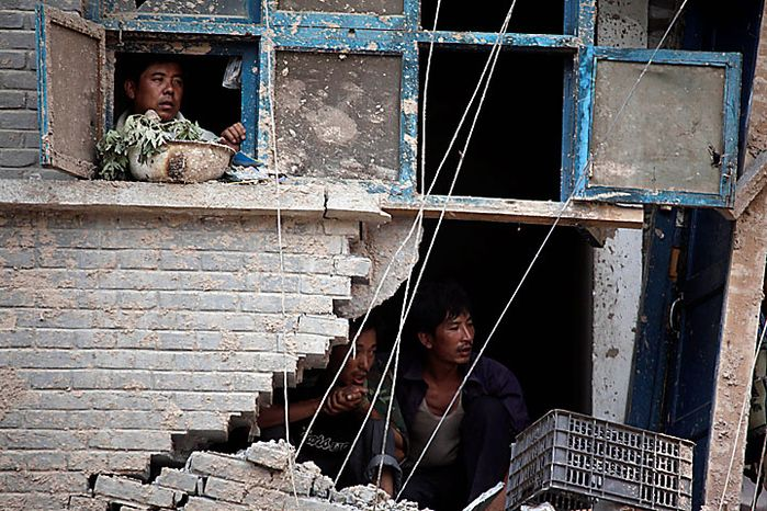 Residents peer out from a mudslide-damaged building in the town of Zhouqu in Gannan prefecture in northwestern China's Gansu province on Monday, Aug. 9, 2010. Rescuers dug through mud and wreckage Monday searching for 1,300 people missing after flash floods and landslides struck northwestern China. (AP Photo/Ng Han Guan)