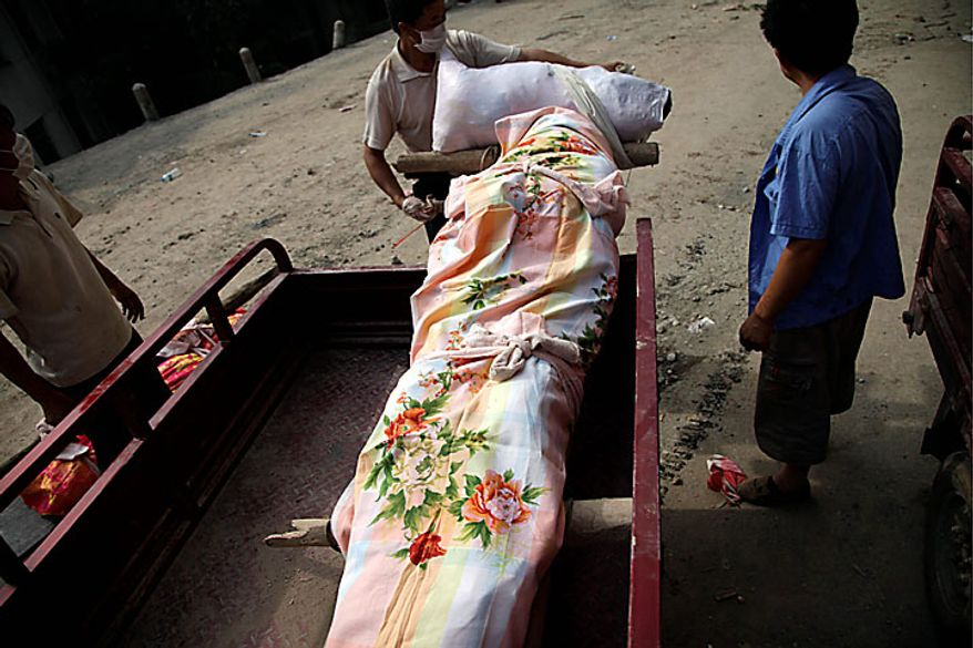 A man prepares to transport a body recovered from the mudslide-devastated town of Zhouqu in Gannan prefecture in northwestern China's Gansu province on Monday, Aug. 9, 2010. Rescuers dug through mud and wreckage Monday searching for 1,300 people missing after flash floods and landslides struck northwestern China. (AP Photo/Ng Han Guan)