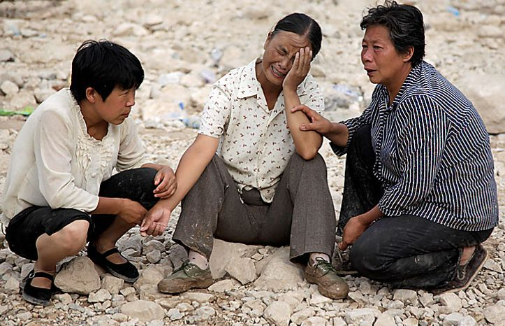 A grieving woman is consoled by others at the mudslide-hit town of Zhouqu in Gannan prefecture in northwestern China's Gansu province on Monday, Aug. 9, 2010. Rescuers dug through mud and wreckage Monday searching for 1,300 people missing after flash floods and landslides struck northwestern China. (AP Photo/Ng Han Guan)