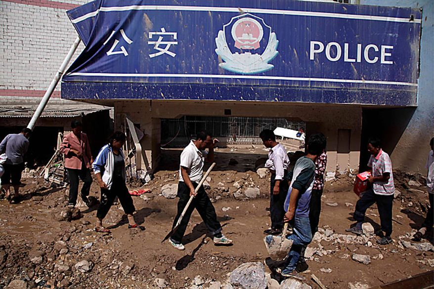 Residents walk past a police station covered by a mudslide in the town of Zhouqu in Gannan prefecture in northwestern China's Gansu province on Monday, Aug. 9, 2010. Rescuers dug through mud and wreckage Monday searching for 1,300 people missing after flash floods and landslides struck northwestern China, just one of a series of floods across Asia that have killed hundreds and spread misery to millions more. (AP Photo/Ng Han Guan)