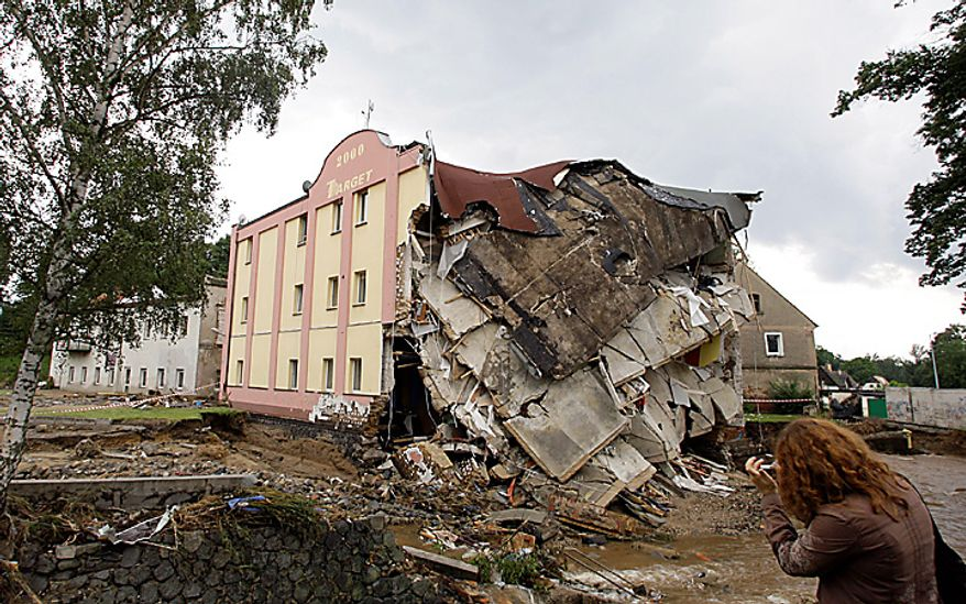 A woman  takes a picture of house that collapsed in flash floods that hit the town of Bogatynia, Poland, Monday, Aug. 9, 2010. Poles, Czechs and Germans struggled Monday to clean up homes and towns badly damaged as the waters of deadly weekend flooding began to recede. But the swollen rivers pushed northward, and other towns and villages braced for possible high waters.  The floods caused a number of fatalities. (AP Photo/Petr David Josek)