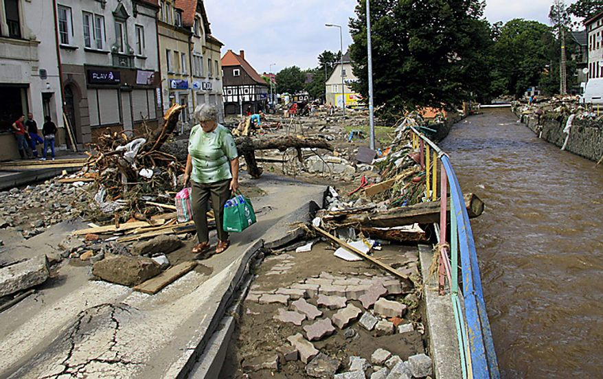 A resident walks on a destroyed  street after flash floods in the town of Bogatynia, Poland, Monday , Aug. 9, 2010. The flooding has struck an area near the borders with Germany and the Czech Republic, where there have also been several fatalities. (AP Photo/Robert  Steiner )