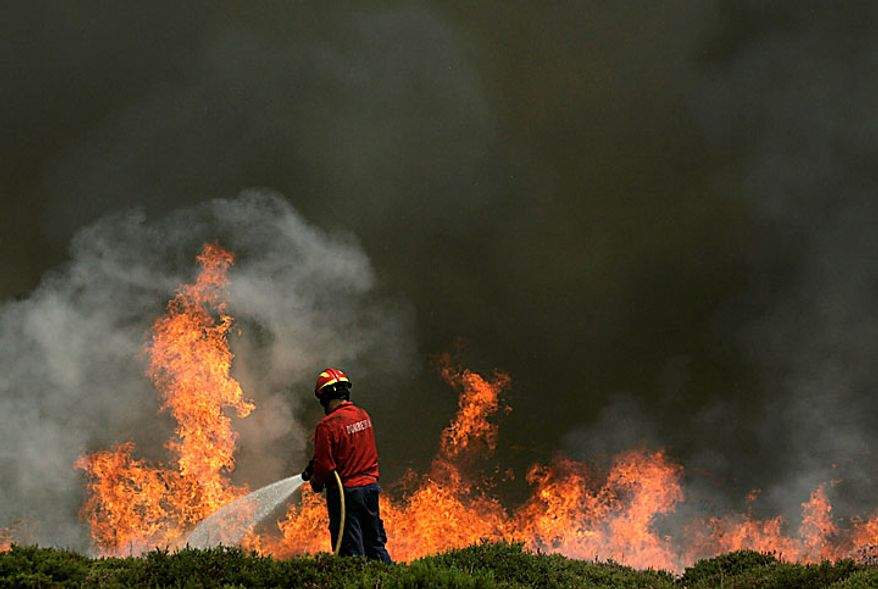 A firefighter works on a fire front on Arada Mountain near Sao Pedro do Sul, Portugal, on Monday, Aug. 9, 2010. Firefighters were continuing to battle raging brush fires on Monday. They say some have been contained but others still are burning out of control. (AP Photo/Francisco Seco)