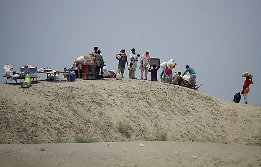 Villagers take shelter on higher ground as flood waters threaten the area in Ghazi Gat near Muzaffargarh in central Pakistan on Monday, Aug. 9, 2010. The number of people suffering from the massive floods in Pakistan exceeds 13 million -- more than the combined total of the 2004 Indian Ocean tsunami, the 2005 Kashmir earthquake and the 2010 Haiti earthquake, the United Nations said. (AP Photo/K.M. Chaudary)