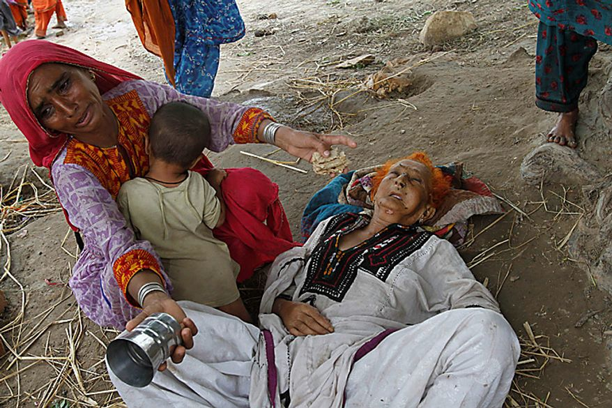 A woman affected by the flooding in Pakistan sits next to her mother, Deenal Mai, 75, who is ill and exhausted because of hunger and thirst, on their arrival at Sukkur in Pakistan's Sindh Province on Monday, Aug. 9, 2010.  The number of people suffering from the massive floods in Pakistan exceeds 13 million -- more than the combined total of the 2004 Indian Ocean tsunami, the 2005 Kashmir earthquake and the 2010 Haiti earthquake, the United Nations said. (AP Photo/Shakil Adil)