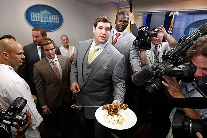 New Orleans Saints tackle Zach Strief serves Gulf shrimp and andouille sausage skewers in the briefing room of the White House in Washington on Monday, Aug. 9, 2010, after a ceremony in which President Obama honored of the 2009 NFL Super Bowl-winning New Orleans Saints. At left is White House Assistant Chef Sam Kass. (AP Photo/Charles Dharapak)