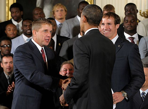 President Obama (center) shakes hands with New Orleans Saints football coach Sean Payton (left) as Saints quarterback Drew Brees (right) looks on during a ceremony honoring the 2009 Super Bowl champion New Orleans Saints on Monday, Aug. 9, 2010, in the East Room of the White House in Washington. (AP Photo/Susan Walsh)