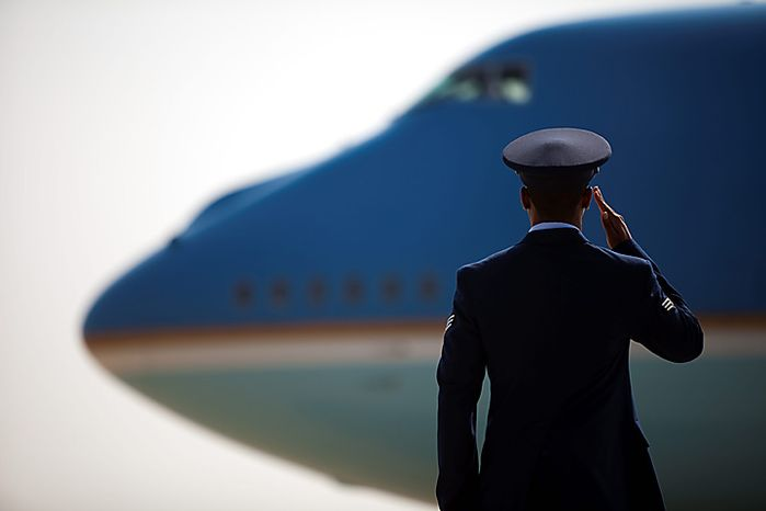 An Air Force member salutes as Air Force One prepares for take-off with President Barack Obama aboard, Monday, Aug. 9, 2010, at Andrews Air Force Base, Md. (AP Photo/Drew Angerer)