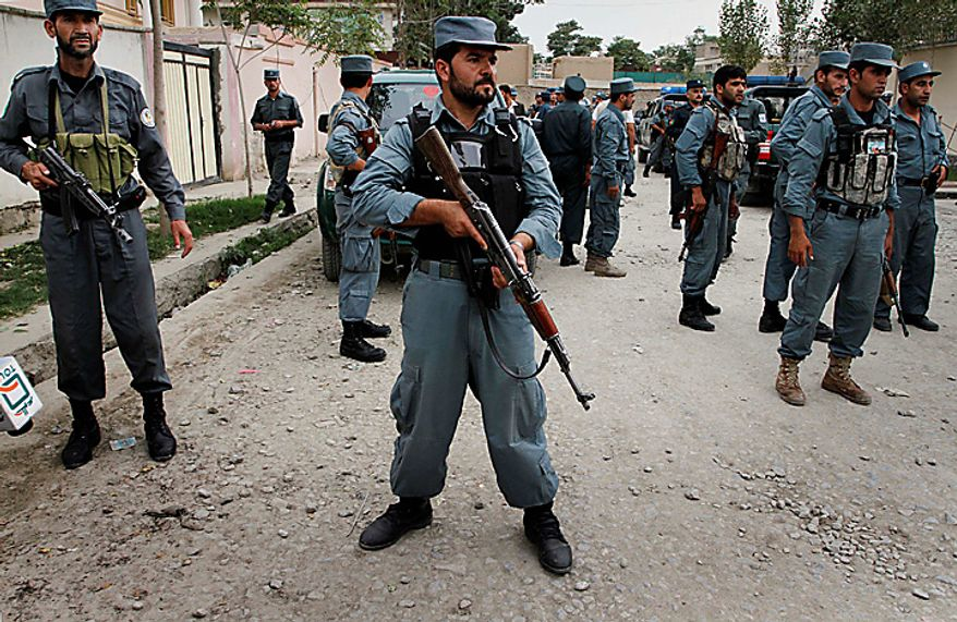 Afghan police officers block traffic near the scene of a militant attack in Kabul, Afghanistan on Tuesday, Aug. 10, 2010. Two suicide attackers struck a building rented by a private security company in Afghanistan's capital Tuesday, detonating their explosive vests to kill two company drivers, police said. (AP Photo/Musadeq Sadeq)