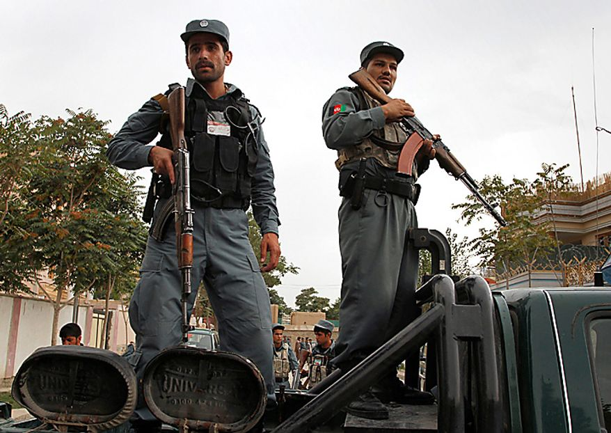 Afghan police officers stand alert on the back of a police pickup truck at the scene of militants attack in Kabul, Afghanistan on Tuesday, Aug 10, 2010. Two suicide attackers struck a building rented by a private security company in Afghanistan's capital Tuesday, detonating their explosive vests to kill two company drivers, police said. (AP Photo/Musadeq Sadeq)