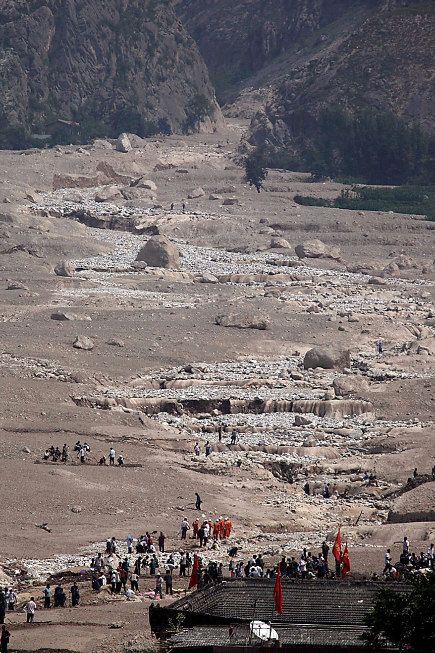 Chinese rescue workers and residents dig in the mud for victims of Sunday's mud slide that swept into the town of Zhouqu in Gannan prefecture of northwestern China's Gansu province, Tuesday, Aug. 10, 2010. Rescuers in three countries across Asia struggled to reach survivors from flooding that has afflicted millions of people. (AP Photo/Ng Han Guan)