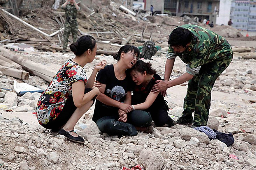 Chinese residents grieve amongst the rocks and debris after a mudslide swept into the town of Zhouqu in Gannan prefecture of northwestern China's Gansu province, Tuesday, Aug. 10, 2010. Rescuers in three countries across Asia struggled Tuesday to reach survivors from massive flooding that has afflicted millions of people, as the death toll climbed in the remote Chinese town where hundreds died and more than 1,100 were missing from landslides. (AP Photo/Ng Han Guan)