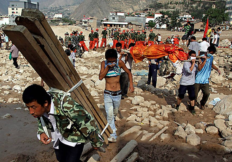 A Chinese man uses his shirt to cover from the stench as others carry a corpse across the rock and debris left by Sunday's mud slide that swept into the town of Zhouqu in Gannan prefecture of northwestern China's Gansu province, Tuesday, Aug. 10, 2010. Rescuers in three countries across Asia struggled to reach survivors from flooding that has afflicted millions of people. (AP Photo/Ng Han Guan)
