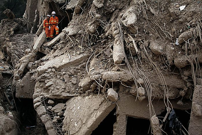 A rescue worker yawns as he stands with a colleague amongst the remains of a collapsed building after a mudslide swept through the town of Zhouqu in Gannan prefecture of northwestern China's Gansu province, Tuesday, Aug. 10, 2010. Rescuers in three countries across Asia struggled Tuesday to reach survivors from massive flooding that has afflicted millions of people, as the death toll climbed in the remote Chinese town where hundreds died and more than 1,100 were missing from landslides.  (AP Photo/Ng Han Guan)